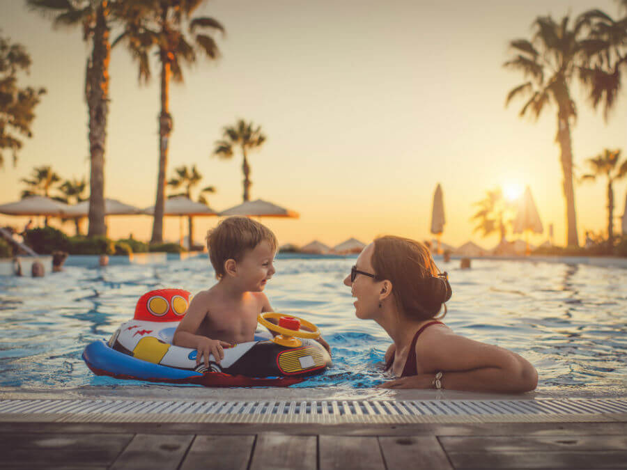 Mother and son swimming in a resort pool